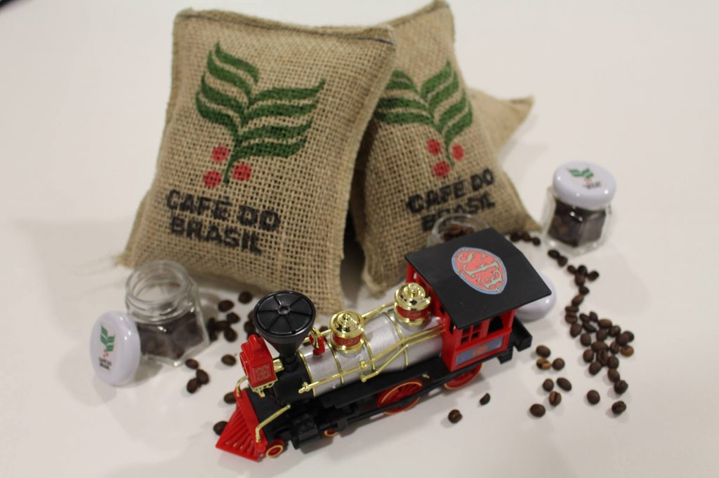 """Foto colorida de 3 sacos de juta apoiados uns sobre os outros.Neles estão escritos """"Café do Brasil"""". Na frente dos sacos um trenzinho no estilo Maria Fumaça. Espalhados aop redor destes objetos, grãos de café."""