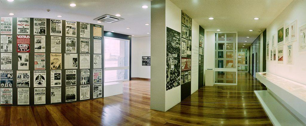 Foto colorida de espaço expositivo com piso de madeira. Vemos, no canto direito, uma parede com vários cartazes. No centro um painel com fotos grandes e no canto direito uma vitrine na altura da cintura.