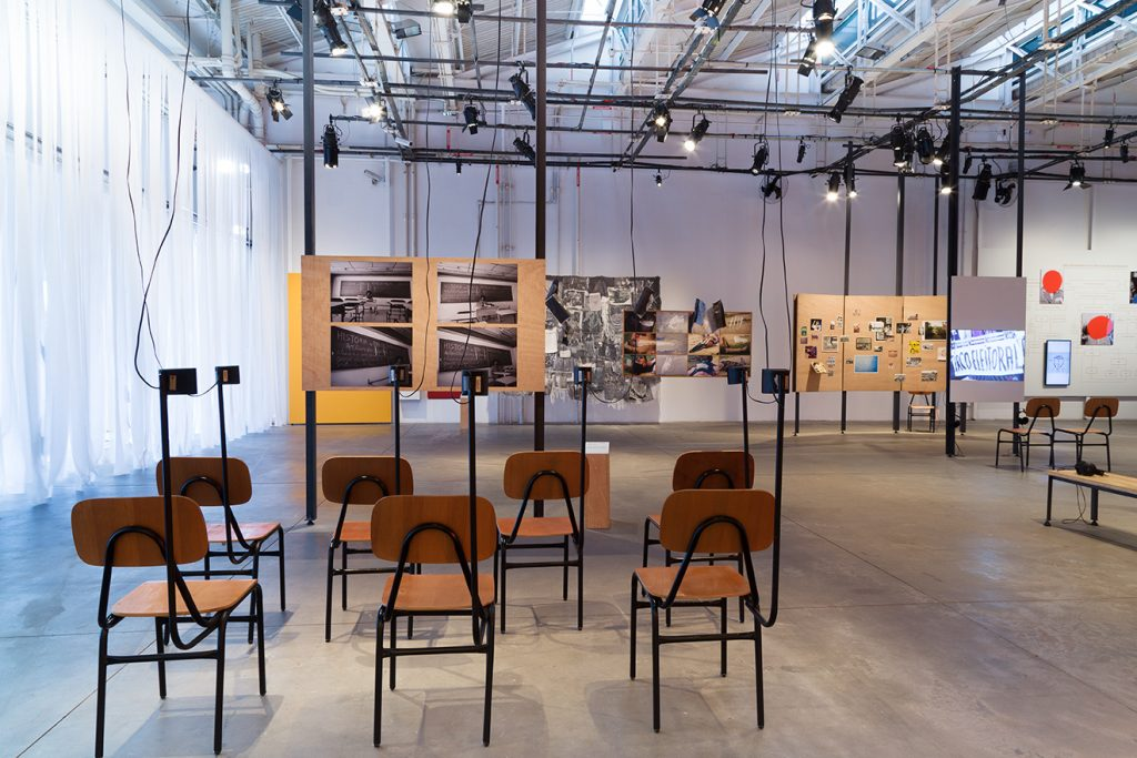 Foto de 7 cadeiras escolares dispostas em duas fileiras de modo a olhar um painel de madeira com 4 fotos de lousa escolar. Nas cadeiras das pontas pequenas caixas de som.