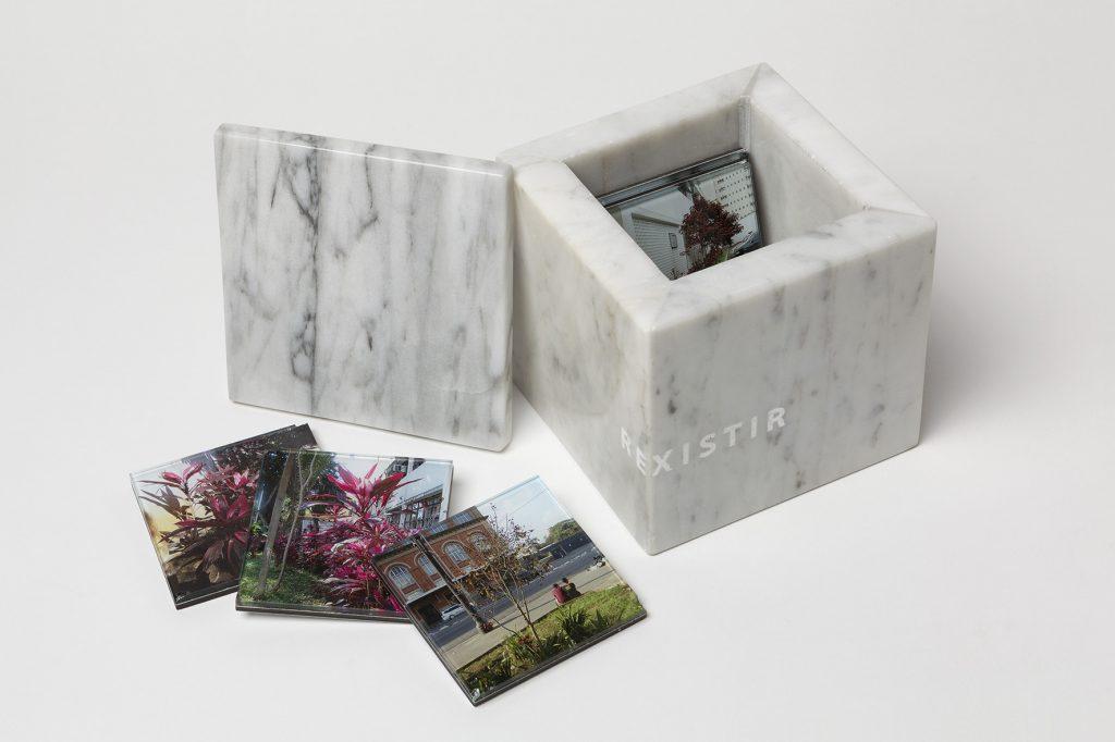 """Foto de uma caixa de mármore branco com fotos coloridas dentro. Na lateral esquerda da caixa há 3 fotos coloridas, sendo 2 de uma planta de cor roxa e outra de uma praça com 2 pessoas sentadas e um grande prédio de tijolos a vista e janelas amplas ao fundo. Gravado na lateral da caixa a palavra """"Rexistir"""""""