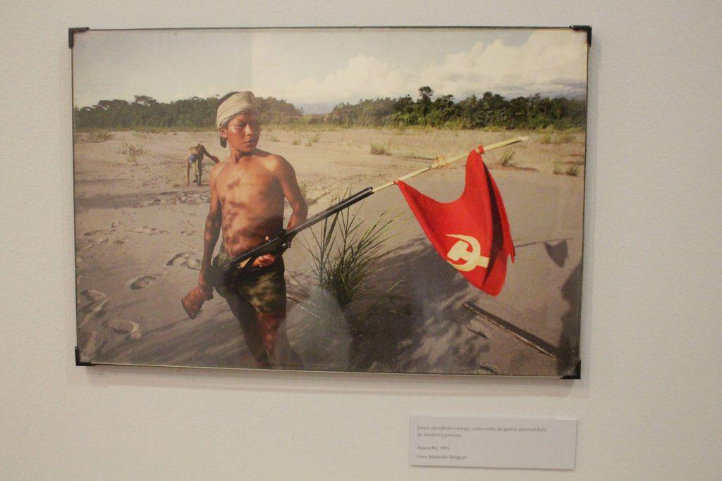 Foto de um quadro fotográfico colorido com a figura de um homem sem camisa e usando bermuda, com um lenço na cabeça e segurando uma bandeira vermelha com o desenho de uma foice e um martelo em branco.