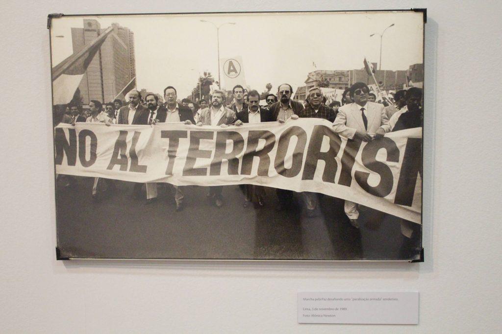 """Foto de um quadro fotográfico preto e branco um grupo de homens que marcham segurando uma faixa onde lê-se """"no al terrorismo""""."""