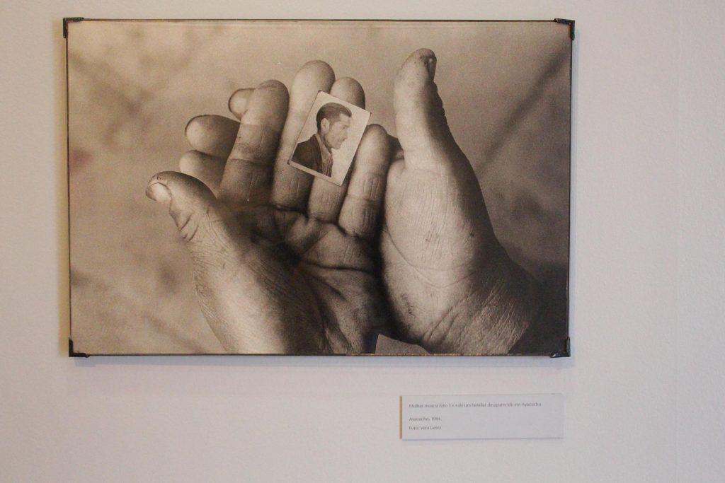 Foto de um quadro fotográfico preto e branco de mãos pequenas e com marcas de terra que seguram foto em 3x4 e um rosto masculino de perfil.