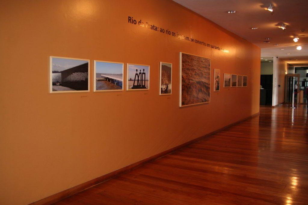"""Foto colorida de uma parede branca de sala de exposição com piso de madeira.Pregados na parede, vemos quadros onde todos vemos água com diferentes construções ao redor. Na parede conseguimos ler os escritos """"Rio da Prata"""" o outras palavras que não conseguimos identificar pela foto."""