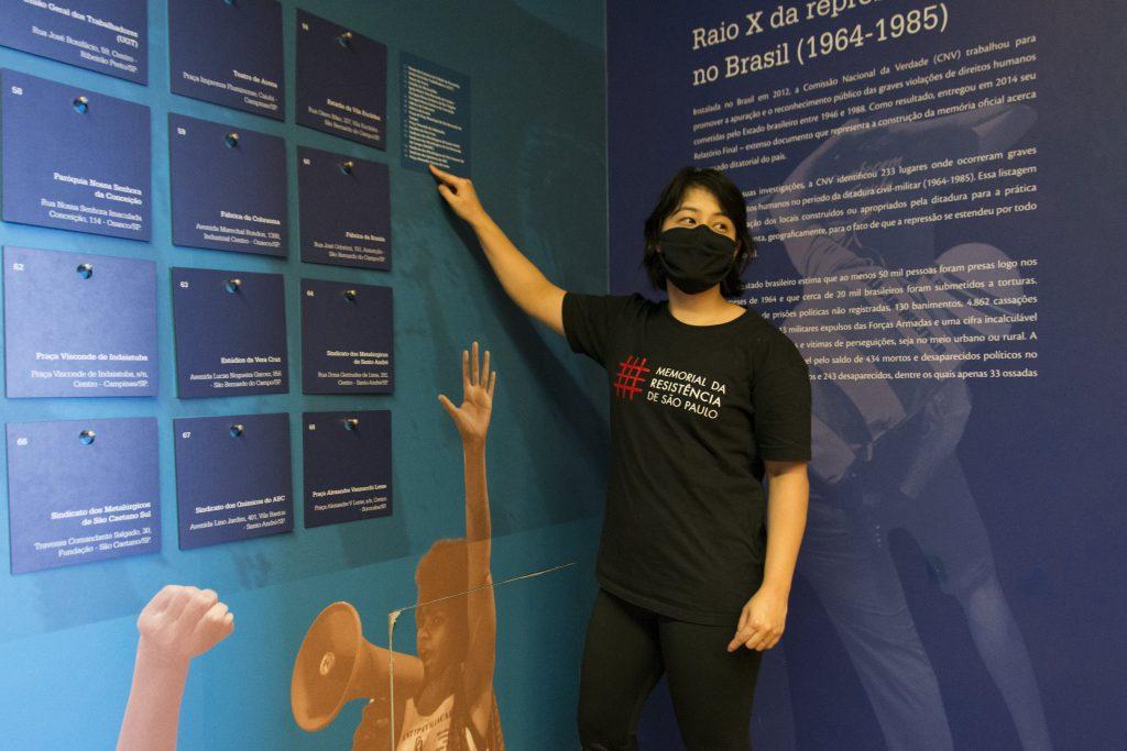 """Foto de educadora usando mascara facial eu camiseta preta com a logomarca do Memorial aponta para um texto que está na parede. Na parede que é azul, um pouco abaixo do texto que ela aponta há a imagem de uma mulher negra com o braço esquerdo para cima e falando em um megafone. Atrás dela, escrito em outra parede lemos """" Raio x da repressão no Brasil (1964-1985)"""