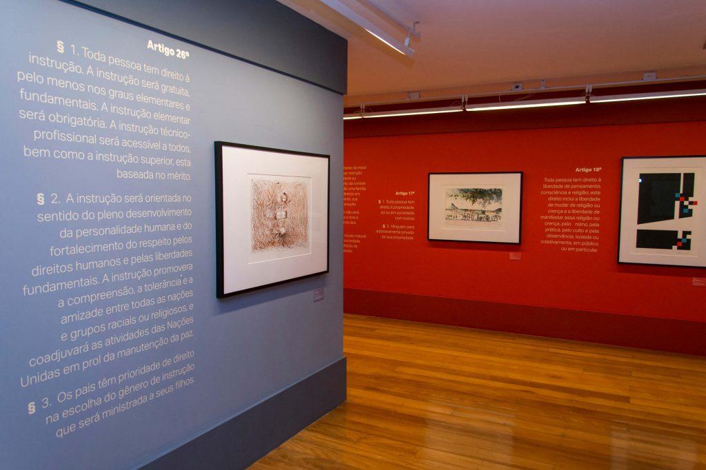 Foto do espaço expositivo onde no canto esquerdo aparece uma parte da parede azul clara com um texto em letras brancas e um quadro com coloração marrom. No fundo observa-se uma parede vermelha com dois quadros e com blocos de textos brancos nos lados esquerdos dos quadros.