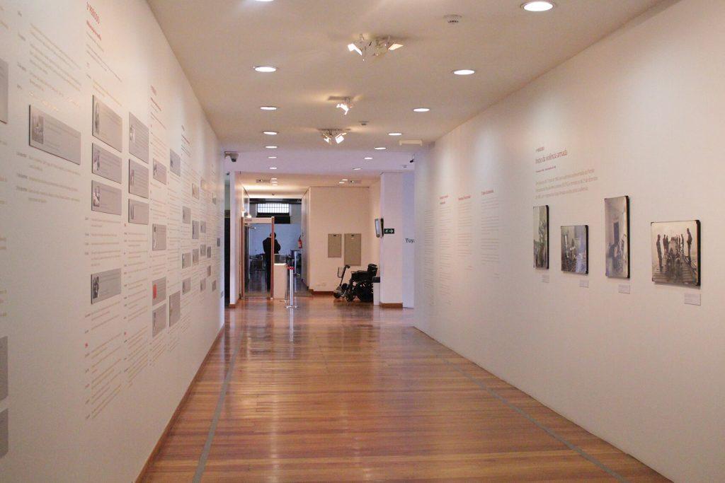 Foto de espaço expositivo com paredes paralelas. Na parede da direita vemos 4 quadros fotográficos coloridos. Na parede da esquerda vemos pequenas placas com informações e textos. O Piso do espaço é de madeira.