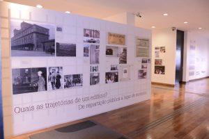 """Fotografia de uma parede branca do espaço expositivo que contém fotografias preta e branca e coloridas espalhadas na parte superior Na parte inferior possui os dizeres: Qual as trajetórias de um edifício? Da repartição pública a lugar de memória""""."""