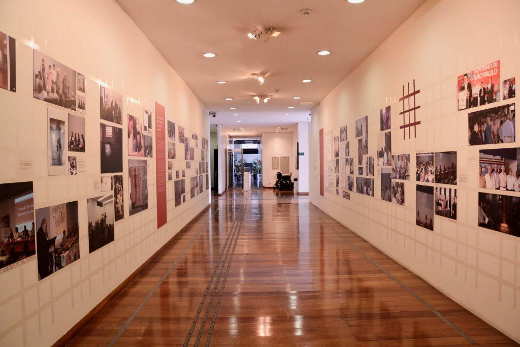 Fotografia do espaço expositivo com paredes paralelas. Na parede da direita vemos várias fotografias espalhadas com a logomarca do Memorial em vermelho no centro superior . Na parede da esquerda vemos mais fotografias coloridas espalhadas, entre essas fotografias há um bloco de texto laranja. O piso do espaço é de madeira.