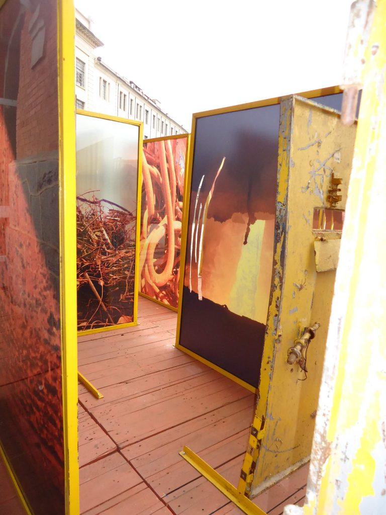 Foto de painéis de metal pintado de amarelo com fotos coloridas de espaços em ruínas sobre um tablado de madeira.