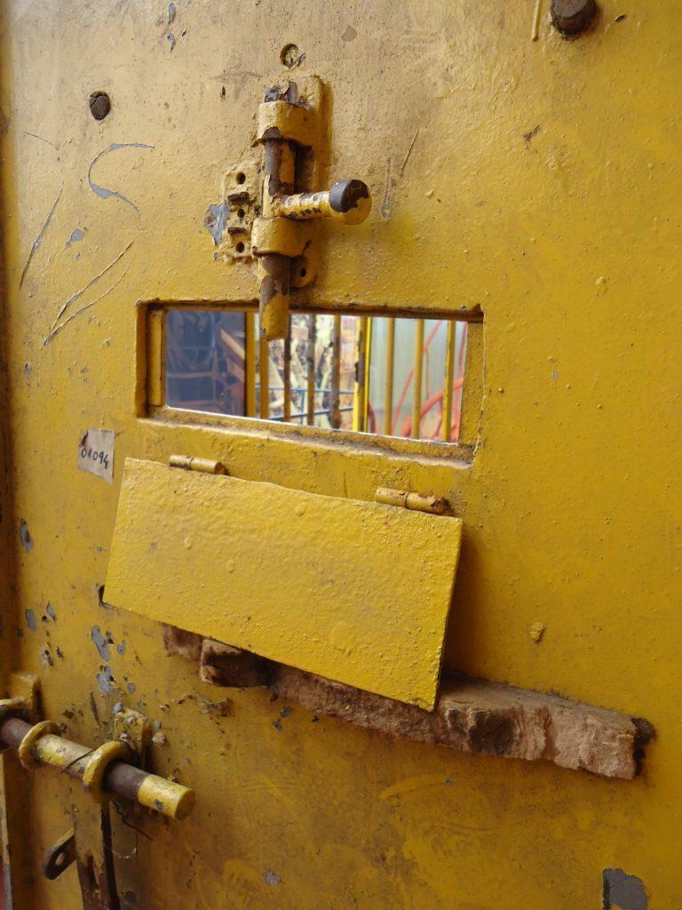 Foto de uma porta de cela de metal pintada de amarelo. No detalhe da imagem vemos uma pequena abertura no centro e trincos na parte superior e na lateral esquerda.
