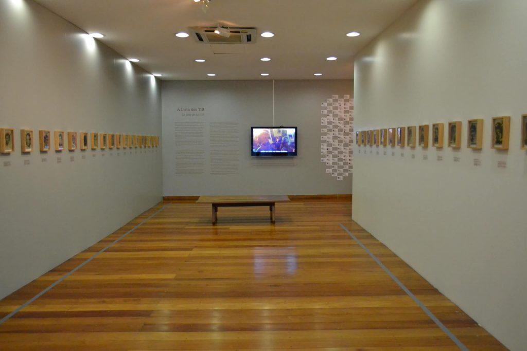 Foto de espaço expositivo de paredes verdes claro. Nas paredes das laterais vemos quadros de 20cm x 15cm com molduras de madeira clara. Ao fundo uma televisão com uma imagem colorida. O é de madeira e há um banco de madeira em frente a tv.