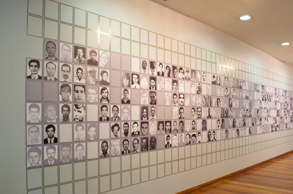 Foto de parede branca em que parece plotado muitas fotos 3x4 de homens e mulheres em preto e branco, formando um quadriculado. Neste quadriculado, por entre as fotos, aparecem alguns espaços vazios.