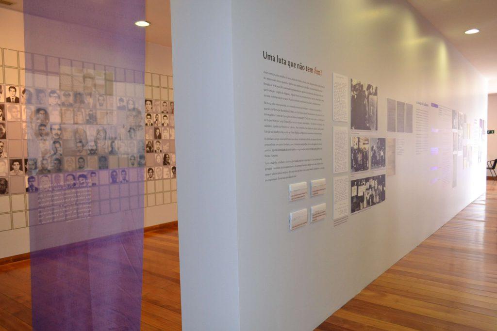 """Foto de espaço expositivo com 2 paredes brancas paralelas. Na parede à esquerda vemos várias fotos 3x4 de homens e mulheres em preto e branco. Na parede da direita, fotos em preto e branco e textos em preto. Nela podemos ler """" Uma luta que não tem fim"""". No canto esquerdo da foto vemos um tecido azul transparente pendurado no teto."""