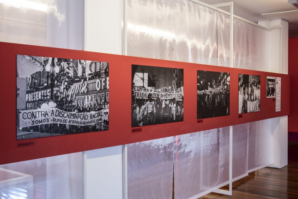 Fotografia de um dos painéis da exposição, onde ao fundo observa-se um tecido translúcido brilhante do teto ao chão que pega toda a extensão do painel a sua frente. Esse painel é de formato retangular e de cor vermelha, está suspenso por estruturas metálicas brancas e contém 5 fotografias em preto e branco de um grupo de pessoas se manifestando.