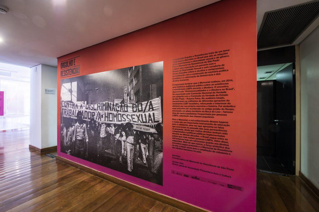 """Fotografia de uma parede da exposição com efeito degradê com as cores vermelha e rosa, sendo vermelho na parte superior e rosa na parte inferior dessa parede. No canto superior esquerdo da parede está escrito """"Orgulho e Resistências"""" e embaixo há uma grande foto em preto e branco que ocupa todo lado esquerdo da parede. A fotografia em questão é de um grupo de pessoas com uma faixa escrita """"Contra a discriminação do/a trabalhador/a homossexual"""". No canto direito da parede há um bloco de texto com letras pretas dividido em três grandes parágrafos e mais abaixo os autores do texto e as logomarcas do patrocínio da exposição. O chão do ambiente é de madeira e no extremo canto direito da foto é possível ver um mini corredor que leva para uma porta preta aberta no fundo"""