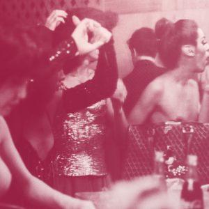 Fotografia preto e branco com filtro rosa de mulheres se maquiando em um camarim. Três delas estão com o braço em frente ao rosto pois arrumam os cabelos, enquanto uma mulher, que é uma figura mais central na fotografia, passa batom. Todas olham para o espelho.