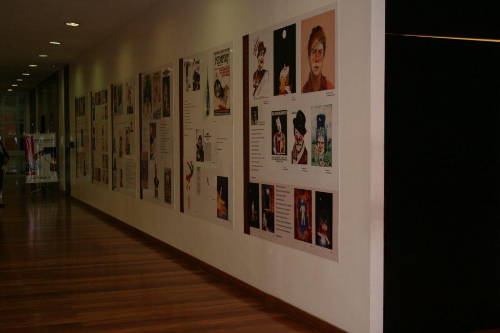 Foto colorida de parede branca com vários cartazes coloridos expostos e alguns escritos. Neles podemos ver figuras humanas.