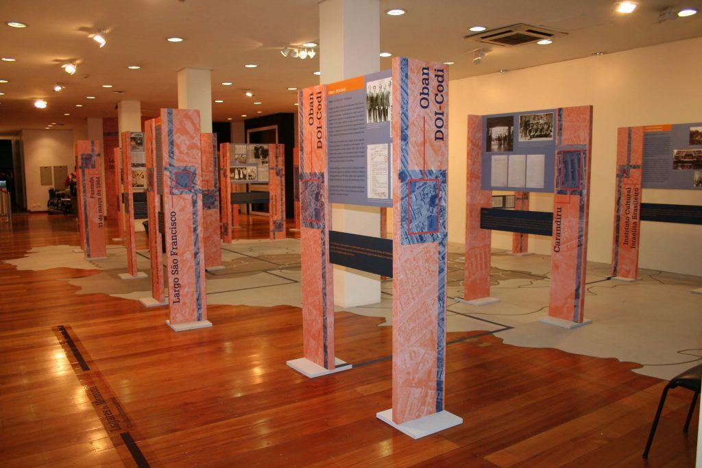 """Foto colorida de painéis espalhados por um espaço expositivo. Suas colunas são estreitas e em um deles vemos um pequeno pedaço de um mapa aéreo com um filtro laranja e com letras azuis lemos """"OBAN/ DOI/CODI"""". O chão do espaço é de madeira e é plotado no piso um mapa com linhas que direcionam até cada um dos painéis."""