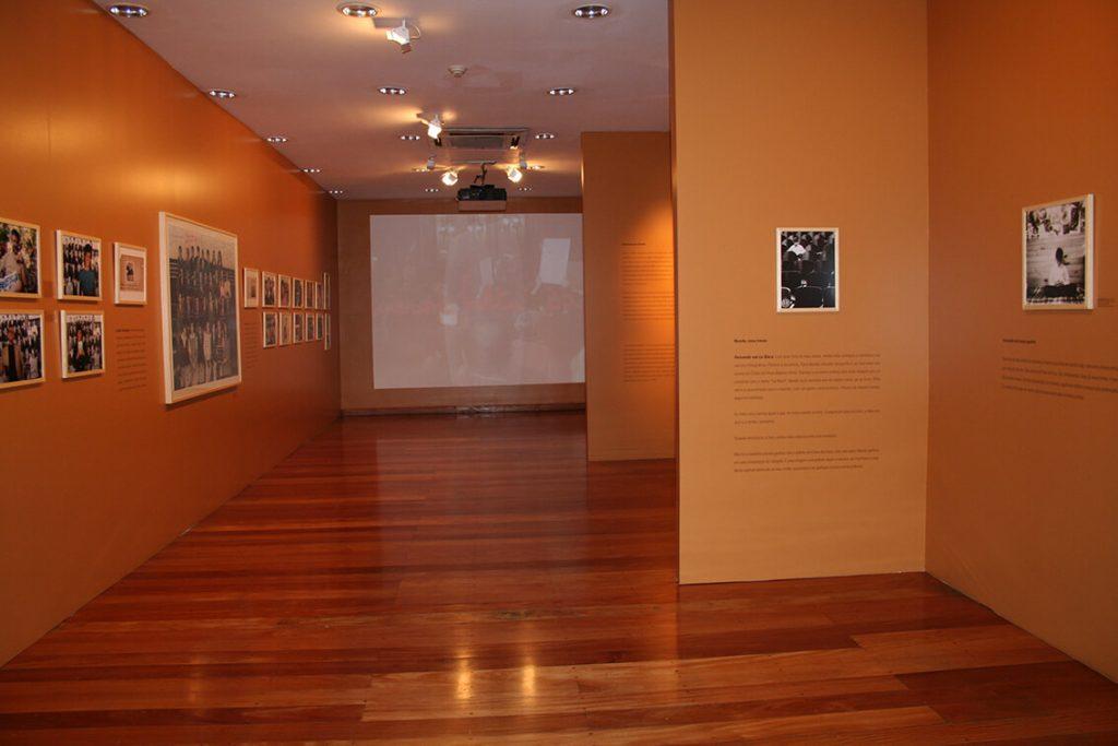 Foto colorida de sala expositiva com quadros com fotografias de pessoas pregados em paredes beges, piso de madeira e uma projeção com vídeo ao fundo.