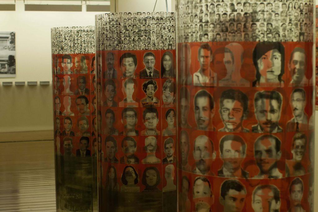 Fotografia de três cilindros feitos de material transparente, onde estão gravadas várias fotografias em preto e branco de rostos de pessoas. As partes centrais dos cilindros possuem uma faixa vermelha que dá destaque às fotografias em preto e branco de rostos de pessoas maiores.