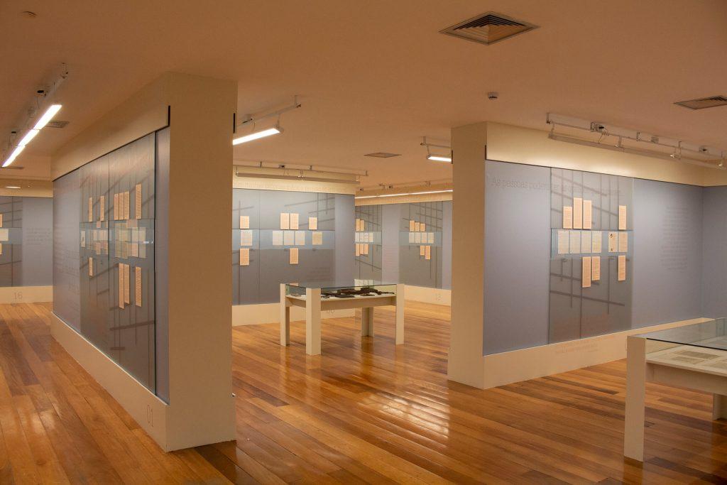 Foto de espaço expositivo de paredes azuis claras com rodapé e beiral brancos. Penduradas em trechos das paredes azuis algumas cartas que estão atrás de vidros.