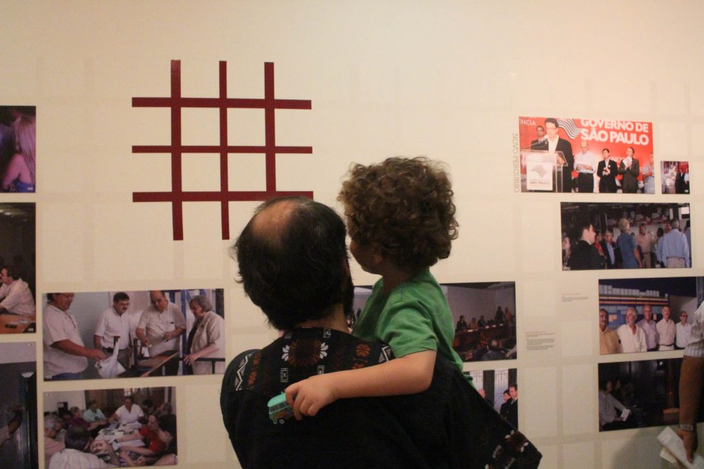 Fotografia colorida com um homem segurando uma criança no colo, ambos estão de costas para a foto e estão olhando para um parede branca com várias fotografias espalhadas ao redor da logomarca do Memorial da Resistência.
