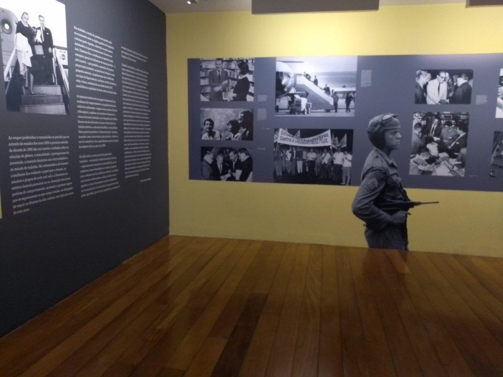 Foto do espaço expositivo onde observa o canto da exposição, pegando duas paredes perpendiculares. A parede da esquerda é cinza escuro com uma fotografia grande preta e branca e blocos de textos em branco. A parede do fundo é amarela claro e na sua faixa central possui um retângulo cinza escuro com fotos em preto e branco. Também no centro dessa parede encontra-se adesivada a figura de um homem de perfil, fardado com uma arma. Esse adesivo vai do chão até a metade da parede. O chão da exposição é de madeira.