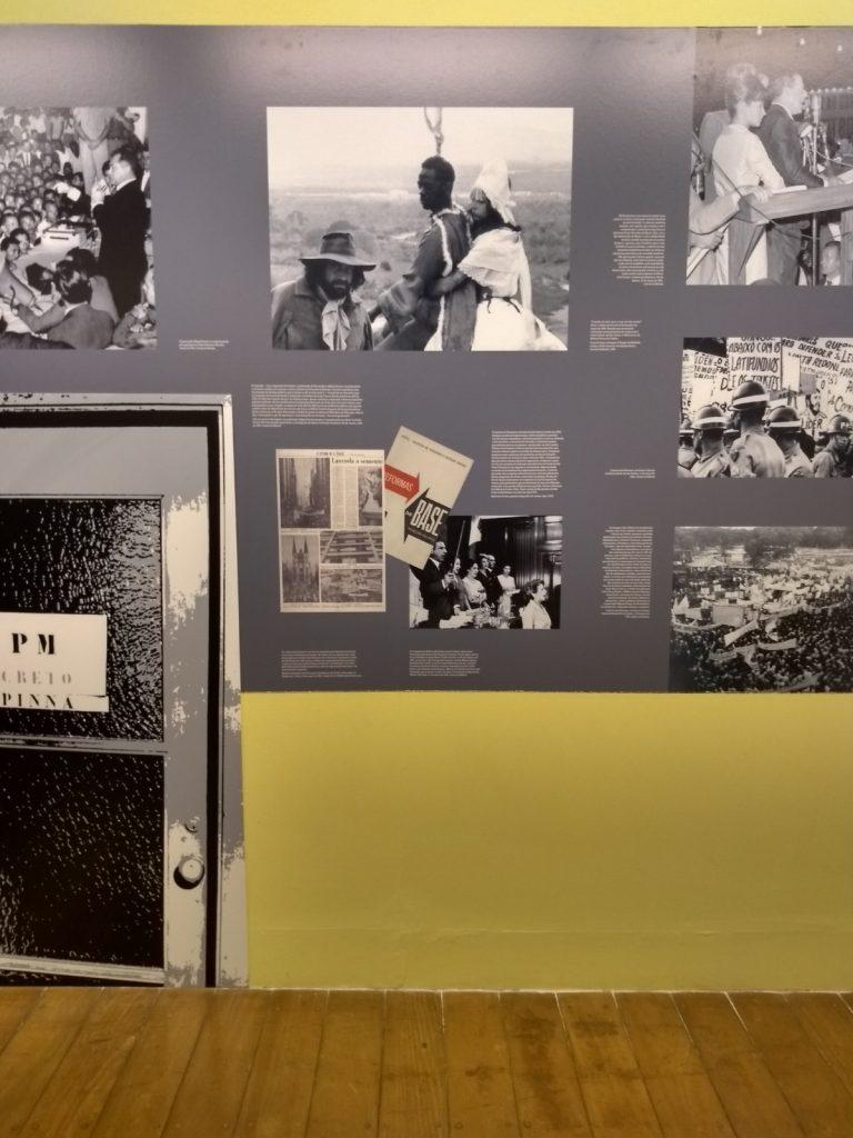 """Foto de uma parte da parede da exposição onde observa-se uma parede amarela claro, do centro da fotografia para a parte superior, tem um retângulo cinza que contém diversas fotos em preto e branco com pequenos blocos de texto. No canto inferior esquerdo da parede tem adesivado do chão até metade do retângulo cinza um desenho de uma porta de vidro em preto e branco com uma placa que Lê-se: """"PM""""."""