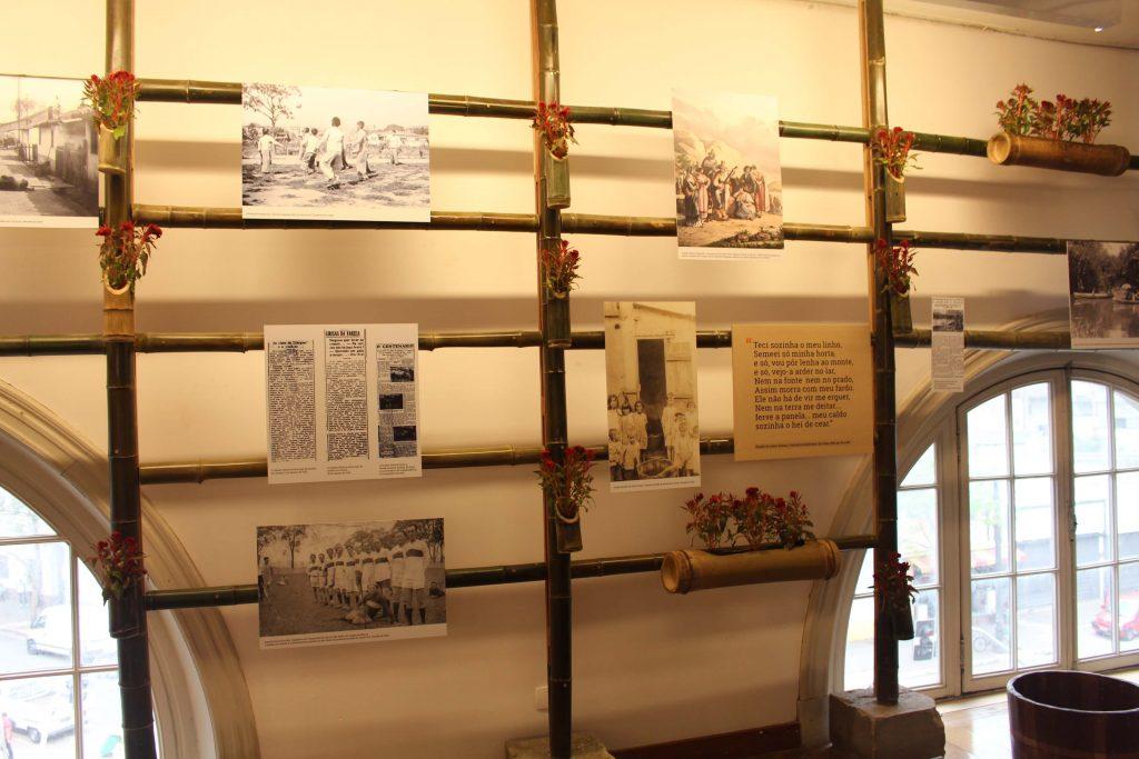 Fotografia de uma parede branca da exposição, onde se observa meio arco de janelas com vidros no chão e sobreposto a essas janelas e parede há uma estrutura de bambu em forma de grades espaçadas. Nessa estrutura de bambu há placas fotográficas em preto e branco e pequenos vasos confeccionados em bambu com flores vermelhas.