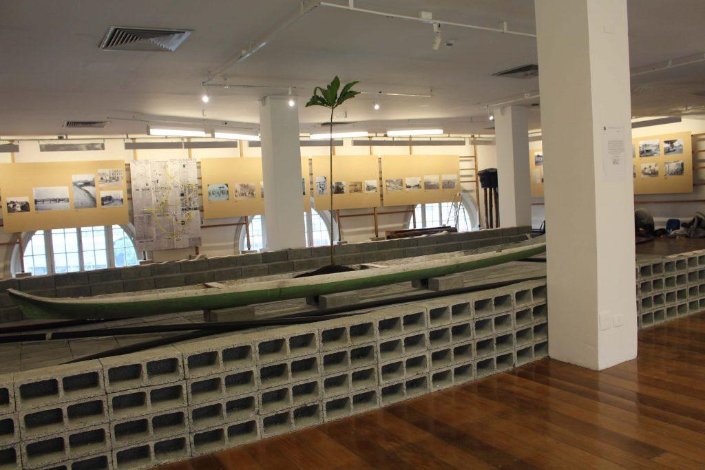 Fotografia de uma obra da exposição que tem uma grande base retangular feita com blocos de concreto vazados. Em cima dessa estrutura há uma grande canoa verde. Há uma coluna branca de formato retangular que fica à frente dessa obra. Ao fundo da fotografia podemos ver painéis amarelos com fotografias. O chão da exposição é de madeira.