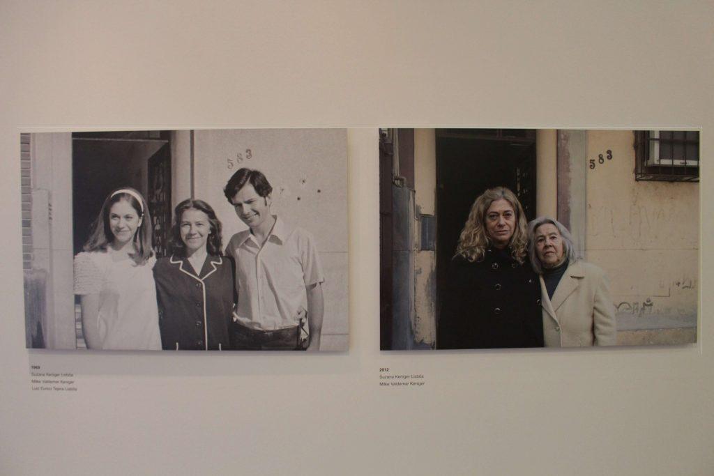 Foto de uma parede branca que contém duas fotografias no centro. A primeira fotografia é em preto e branco e contém três pessoas nela: duas mulheres à esquerda e um homem à direita. A segunda fotografia a esquerda é colorida e é uma réplica da primeira no cenário, mas agora está com somente duas mulheres.