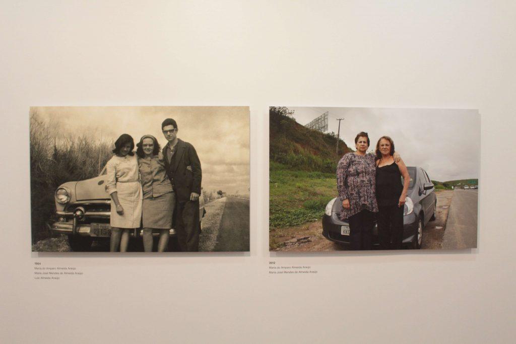 Foto de uma parede branca que contém duas fotografias no centro. A primeira fotografia é em preto e branco e contém três pessoas : duas mulheres à esquerda e um homem à direita na frente de um carro antigo. A segunda fotografia é colorida, replicando o cenário porém com apenas duas mulheres na frente de um carro.