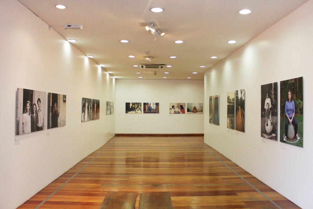 Foto de espaço expositivo de paredes brancas com chão de madeira. Nas paredes das laterais e na parede do fundo vemos quadros fotográficos coloridos e em preto e branco.