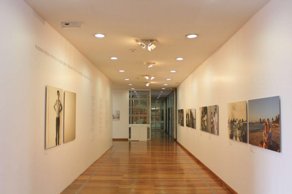 Foto de espaço expositivo de paredes brancas com chão de madeira. Nas paredes das laterais vemos quadros fotográficos coloridos e em preto e branco. Ao fundo observa-se uma grande porta de vidro com a logomarca do Memorial estampada.