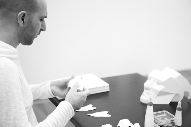 Foto em preto e branco de um homem montando uma máscara em papel, enquanto uma máscara branca já pronta em frente a ele em uma mesa. Na mesa também vemos 2 tubos de cola branca.