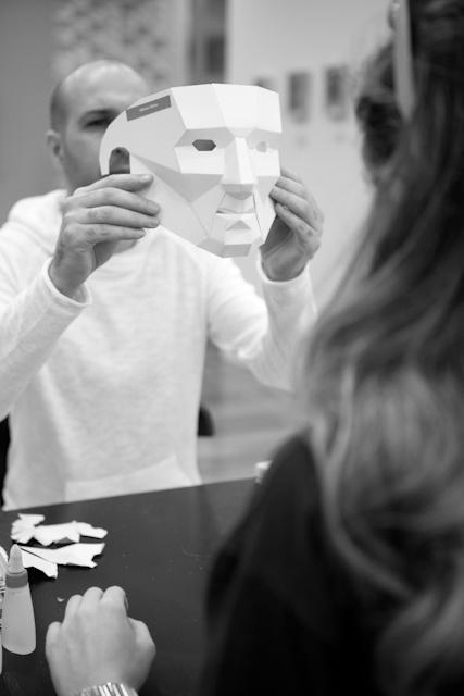 Foto em preto e branco de homem mostrando uma máscara branca de papel para uma mulher. Ele segura a máscara na frente do seu rosto. A mulher está de costas.