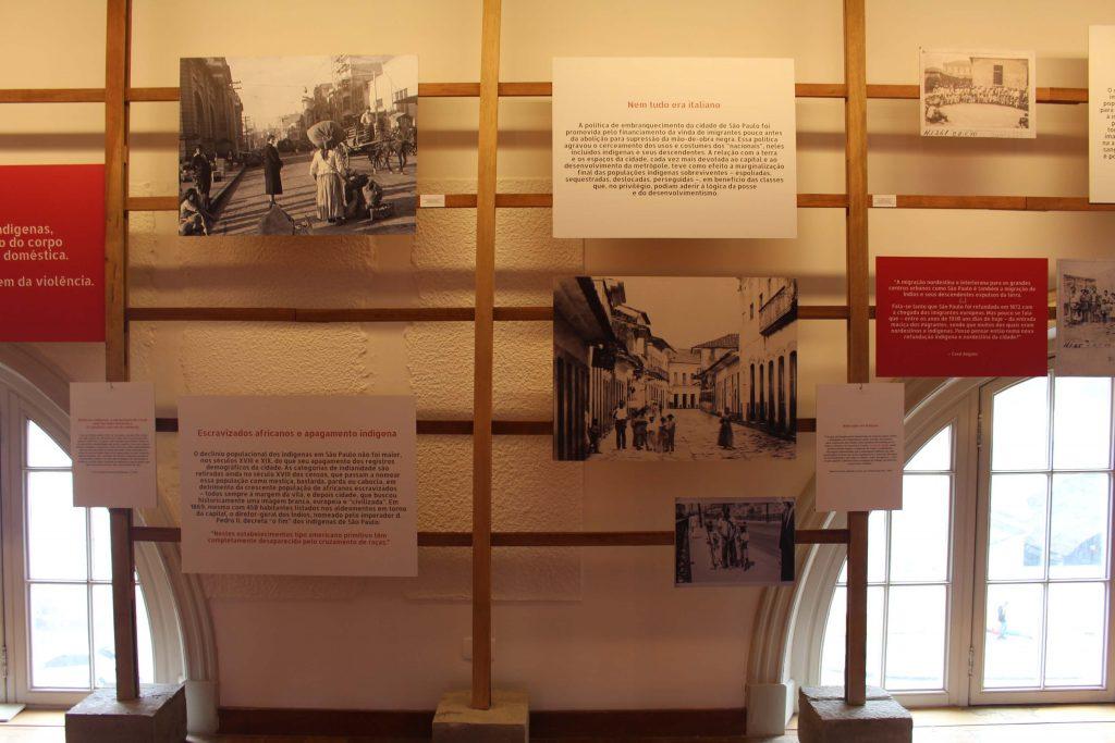 Fotografia de uma parede branca da exposição onde há duas janelas de vidro semicirculares no chão. A frente da parede há uma estrutura de madeira em formato de grade com placas que contém fotografias em preto e branco e placas de textos espalhadas.
