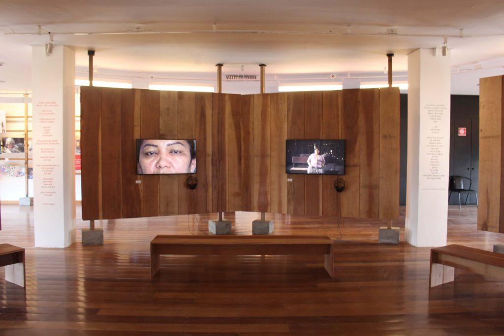 Fotografia do espaço expositivo onde se observa duas colunas brancas de formato retangular do teto ao chão, entre essas colunas há dois painéis de madeira suspensos por uma estrutura também de madeira, com um aparelho televisor no centro de cada, acompanhado de um fone de ouvido. A frente desses painéis está um banco de madeira.