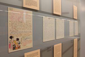 Foto de parede azul clara com cartas em letra cursiva atrás de um vidro. Vemos 5 folhas de papel, sendo que a primeira delas há o desenho de duas gueixas. Acima destas cartas, seu conteúdo é digitado em placas.