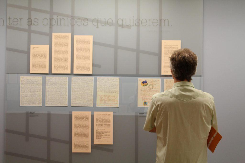 Foto de um homem que veste uma camisa clara observando uma parede azul clara com 6 cartas em letra cursiva atrás de um vidro. Acima e abaixo destas cartas, seu conteúdo digitado em 6 placas.