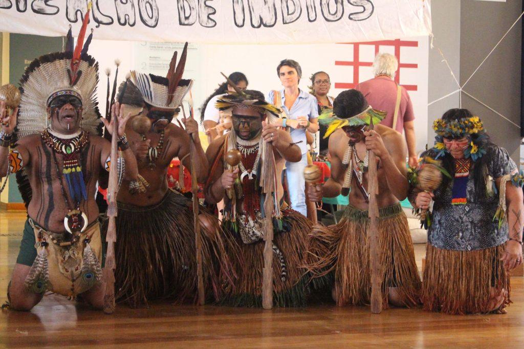 Fotografia de cinco pessoas indígenas, sendo da esquerda para direita 4 homens e 1 mulher, com vestimentas tradicionais como: cocar de penas, colares, saias de palha. Todos estão de joelhos em um chão de madeira e todos seguram um maracá (chocalho utilizado para rituais indígenas). Os homens seguram também uma estaca de madeira apoiada no chão. Ao fundo observamos pessoas visitantes do museu acompanhando a apresentação dos indígenas.