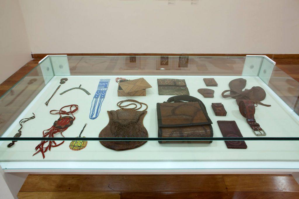 Foto de uma vitrine de base branca com vidro. Nela estão expostos objetos feitos em couro (2 bolsas pequenas, uma carteira, um cinto) e colares, sendo um vermelho e outro azul.
