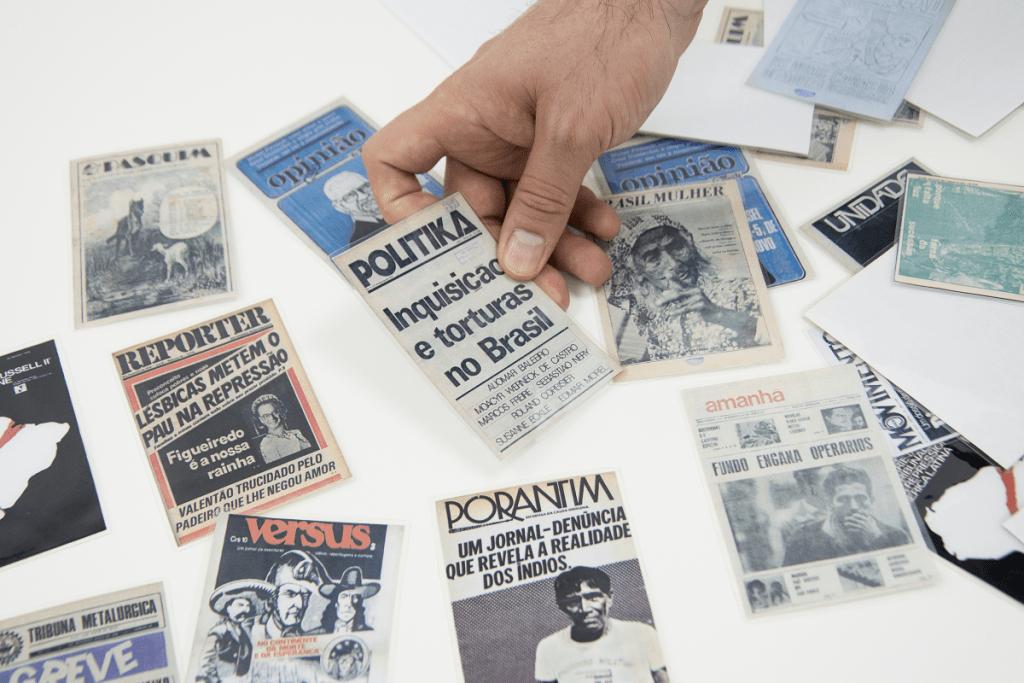 Jogo de cartas em formato pequeno. Cada carta traz uma imagem de capas de veículos de imprensa do período da ditadura civil-militar. As cartas estão embaralhadas em uma mesa e uma mão masculina as manipula.