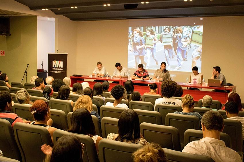 Foto colorida de pessoas em um auditório. Seis delas estão apresentando atrás de uma mesa comprida vermelha, enquanto as demais assistem. Na parede, atrás da mesa vermelha uma projeção de quatro mulheres caminhando na rua.