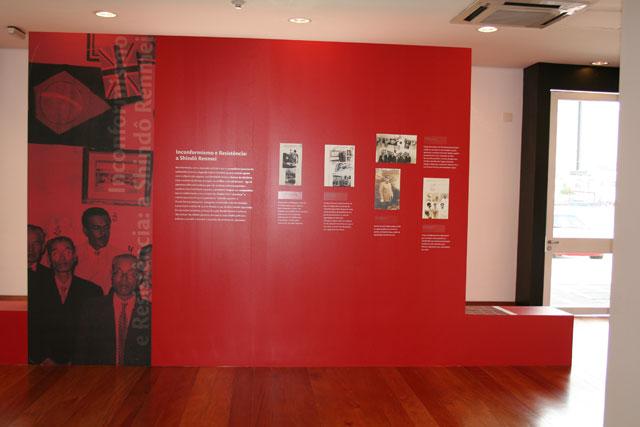 """Foto colorida de uma parede vermelha com plotagem de foto em preto e branco de 5 japonês enfileirados com números escritos em cima de suas cabeças e os escritos """" Inconformismo e Resistência: a Shindô Renntei"""". A parede ainda tem escritos em branco e 5 fotos preto e branco menores."""
