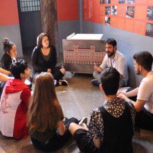 Na foto colorida e desfocada, oito pessoas estão sentadas no chão em um círculo enquanto um homem de barba fala e os demais prestam atenção. Ele está ao lado de um painel que tem o desenho de um prédio