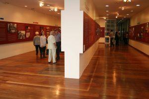 Foto colorida de pessoas visitando um espaço expositivo de paredes brancas com painéis de cor vermelho escuro. Vemos, nos painéis que estão pendurados em paredes brancas, fotos e textos na cor branca. O piso do espaço é de madeira.