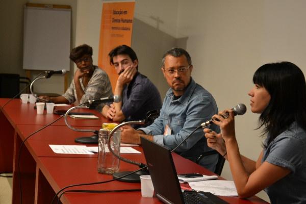 """Foto colorida de quatro pessoas atrás de uma mesa vermelha. Vemos 2 mulheres nas pontas e dois homens no centro. A mulher que está no canto direito fala ao microfone e os demais observam. Atrás na mulher na ponta esquerda vemos um banner onde lemos """"Educação em Direitos Humanos"""""""