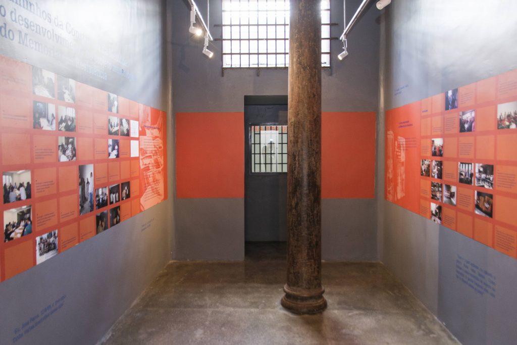 Foto colorida de cela com paredes cinzas onde um faixa laranja de aproximadamente um metro de largura está plotada na parede de forma horizontal a 1 metro e trinta do chão. Nesta faixa vemos muitas fotos coloridas dispostas e textos. No meio da cela vemos uma coluna de ferro. No fundo da foto vemos 2 janelas com grades. O piso é de cimento queimado.